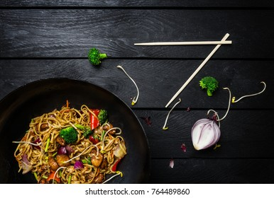 Udon stir fry noodles with chicken and vegetables in wok pan on black wooden background with chopsticks. Top view