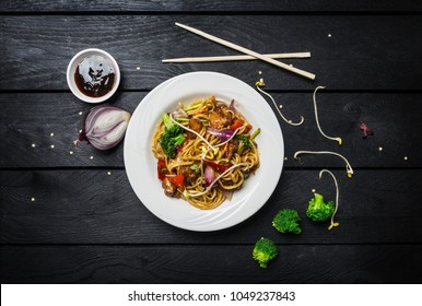 Udon stir fry noodles with meat or chicken and vegetables in a white plate with chopsticks.