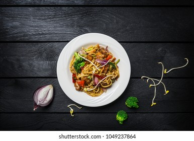 Udon stir fry noodles with meat or chicken and vegetables in a white plate.