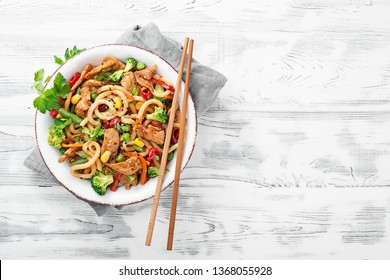 Udon stir fry noodles with pork meat and vegetables in a white plate on white wooden background.