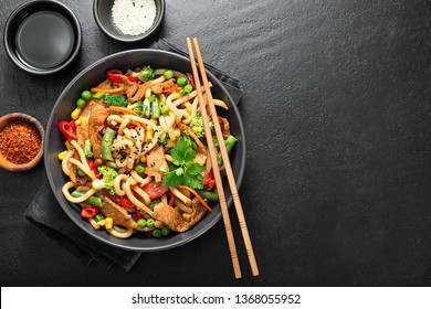Udon stir fry noodles with pork meat and vegetables in a dark plate on black stone background.