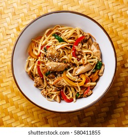 Udon stir-fry noodles with chicken meat and sesame in bowl on bamboo tray background close-up