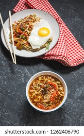 Udon stir-fry noodles with chicken and soup on stone background