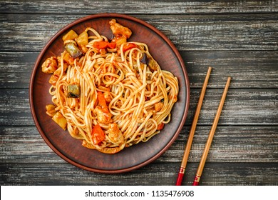 Udon stir-fry noodles with chicken, sweet and sour sauce and food sticks on wooden table top view