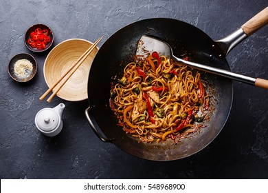 Udon stir-fry noodles with chicken and vegetables in wok pan on dark stone background