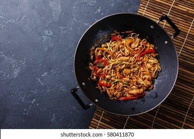 Udon stir-fry noodles with chicken and vegetables in wok pan on dark stone background copy space
