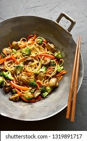 Udon stir-fry noodles with vegetables in wok pan on black stone background. Stir fried vegetables with spaghetti in asian style.