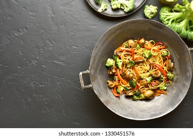Udon stir-fry noodles with vegetables in wok pan on black stone background with copy space. Top view, flat lay