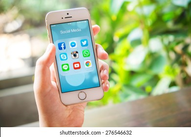 UDON THANI, THAILAND - April 19, 2015: All of popular social media icons on smartphone device screen with hand holding on Apple iPhone 5s.