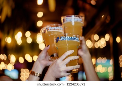 Udon Thani, Thailand October 21, 2018 : Unidentified Girls Happy Holding Large Size Glass of Hoegaarden Draft Belgium Wheat Beer in Pub. Pint of Draft White Beers in Bachelorette Parties.Night Life.