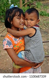 UDONTHANI, THAILAND – JANUARY 14, 2018:  The girl holds younger brother,  her younger brother is stained with mud,  she loves him very much.