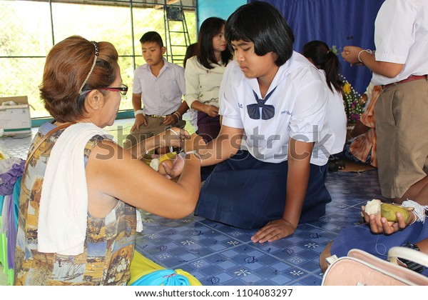 UDONTHANI, THAILAND – MARCH 22, 2018:  Thai student,  elder is binding the wrist and blesses to Thai student,  after she ends primary course,  see her at BAN HUA KUA MUEAD AE school.