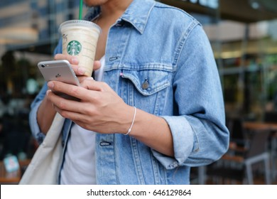 Udonthani,Thailand - May 9,2017 : close up hipster man hand holding iphone and drinking starbuck coffee frappuchino at shopping mall for city lifestyle concept.