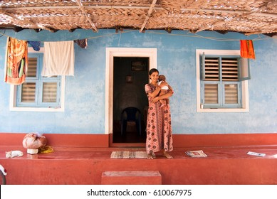 Udupi, Karnataka, India. February 22, 2009. Traditional village house in South India. Unidentified woman and child at home. Udupi, Karnataka, India