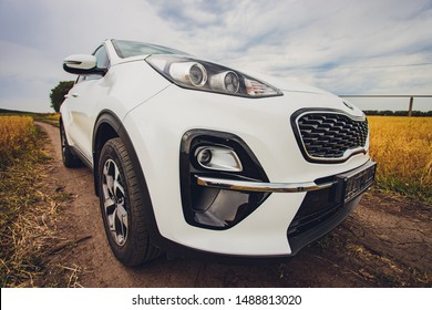 Ufa, Russia, 1 July, 2019: car Kia Sportage 2.0 CRDI awd or 4x4, white color, parked on the road, next to a large rock, with a beautiful blue sky in the background.