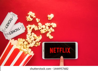 Ufa, Russia - Jule 7, 2019: Table with popcorn bottle and Netflix logo on smartphone. Netflix is a global provider of streaming movies and TV series.