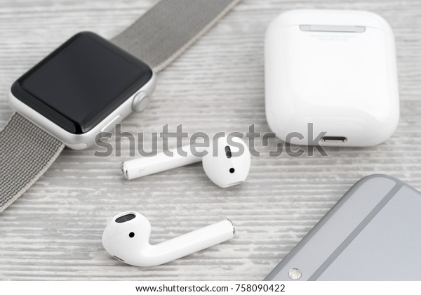 UFA, RUSSIA - OCTOBER 19, 2017: AirPods wireless headphones developed by Apple Inc. AirPods is on the box, apple watch and iphone.