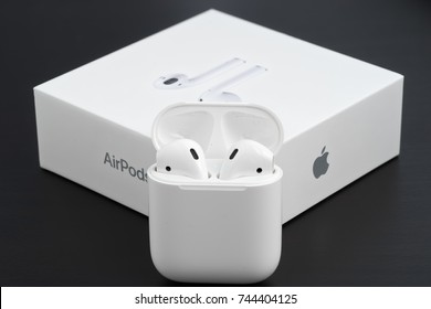 UFA, RUSSIA - OCTOBER 20, 2017: AirPods wireless headphones developed by Apple Inc. AirPods box and charger.