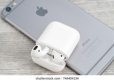 UFA, RUSSIA - OCTOBER 20, 2017: AirPods wireless headphones developed by Apple Inc. AirPods is on the open box and iphone.