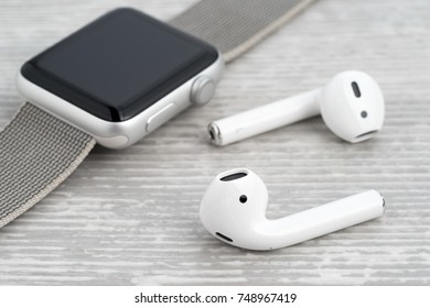 UFA, RUSSIA - OCTOBER 20, 2017: AirPods wireless headphones developed by Apple Inc. AirPods are on the table and apple watch.