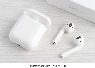 UFA, RUSSIA - OCTOBER 20, 2017: AirPods wireless headphones developed by Apple Inc. AirPods are on the table and box.