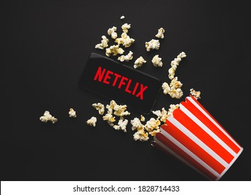 Ufa, Russia - October 7, 2020: Table with popcorn and Netflix logo. Netflix is a global provider of streaming movies and TV series.