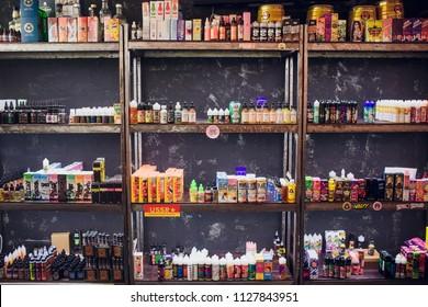 Ufa, Russia, South Vape Shop, 5 July, 2018: E-liquid e-juice High vape for electronic cigarette vaping device , on counter in smoke vapor in vape bar in bottles.