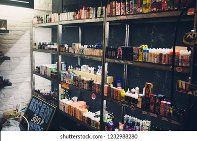 Ufa, Russia, South Vape Shop, 5 November, 2018: E-liquid e-juice High vape for electronic cigarette vaping device , on counter in smoke vapor in vape bar in bottles.