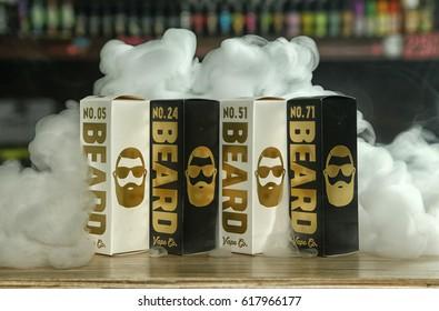 "Ufa, Russia, South Vape Shop, 5 April, 2016: E-liquid (e-juice) ""Beard"" for electronic cigarette (vaping device), on the counter in smoke (vapor) in vape bar in boxes."