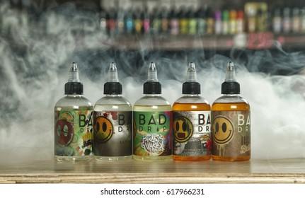 "Ufa, Russia, South Vape Shop, 5 April, 2016: E-liquid (e-juice) ""Bad drip"" for electronic cigarette (vaping device), on the counter in smoke (vapor) in vape bar in bottles."