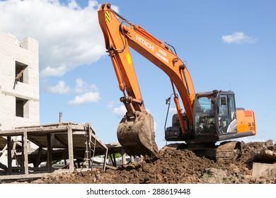 UFA/BASHKORTOSTAN - RUSSIA 13th June 2015 - Orange digger excavates soil in preparation for new apartments for young families in Ufa city Bashkortostan Russia in June 2015