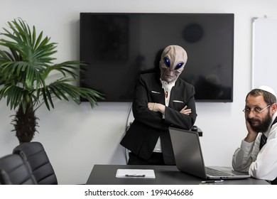 Ufo, Alien business woman looking at camera in the office trying to communicate with Jewish man in kippah at workplace. Alien face with heads and hands in suit. Humanoid image. Alien Extraterrestrial