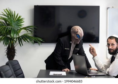 Ufo, Man pointing finger at the a humanoid alien business woman in the office trying to communicate with Jewish man in kippah at workplace. Alien face with heads and hands in suit. Extraterrestrial.
