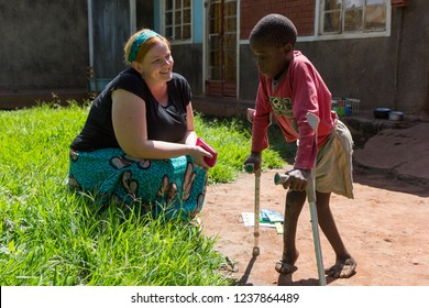 Uganda. 2017/4/28. A white-skinned missionary medical doctor (called 'mzungu' or 'muzungu' by the locals) delights in the progress her patient - a young boy walking with crutches - is making.