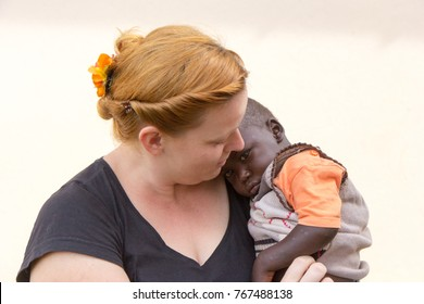 Uganda. April 26 2017. A happy white woman - a missionary - holding an African boy.
