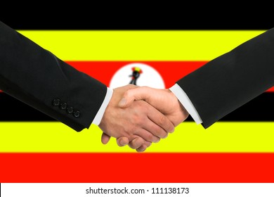 The Uganda flag and business handshake