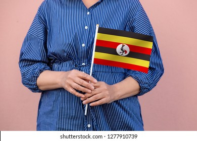 Uganda flag. Close up of woman's hands holding  a national flag of Uganda.