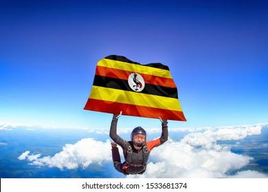 Uganda. Flag in skydiving. People in free fall grab flag of Uganda. Patriotism, men and flag.