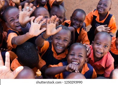 Uganda. June 13 2017. A group of happy primary-school children smiling, laughing and waving. They are dressed in school uniforms.
