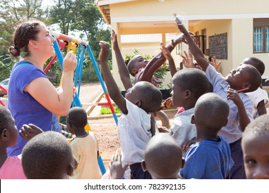 Uganda. June 28 2017. A foreign missionary (Caucasian, called 'mzungu' or 'muzungu' by the locals) blowing soap bubbles and Ugandan children are having fun at that.