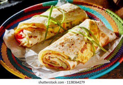 Ugandan Rolex Rolls street food on a brightly colored basket with egg omelette and vegetables rolled in a fried chapati