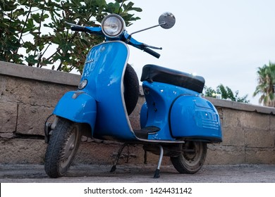 Ugento, Italy - August 23, 2018: 70s blue Scooter Vespa Piaggio parked along the road.