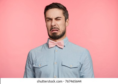 Ugh, how disgusting! Displeased unshaven young male dressed formally, says fie and has dissatisfied facial expression as sees something abominable or detestable, isolated over pink studio background