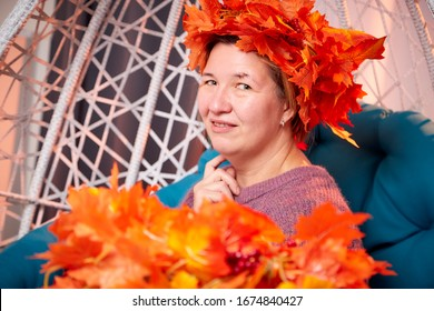 Ugly aged woman in a sweater with a wreath of yellow autumn maple leaves in a white wicker hanging chair in the room with curtains. Old model during photoshoot in studio