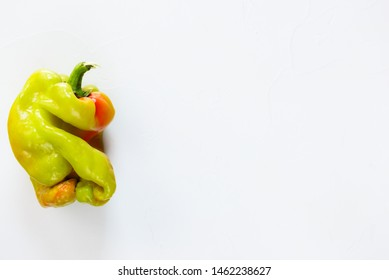 Ugly bell pepper on a white background. Ugly food concept, top view, copy space.