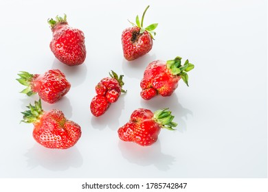 Ugly bright red strawberries with reflection on a white glossy background.
