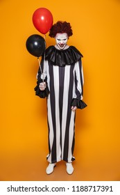 Ugly clown man 20s wearing black costume and halloween makeup grimacing and holding balloons isolated over yellow background