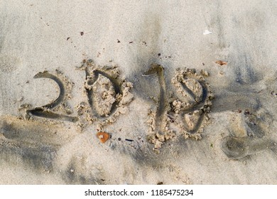 ugly and clumsy letters 2018 on sandy beach, concept of the outgoing year. Rough texture