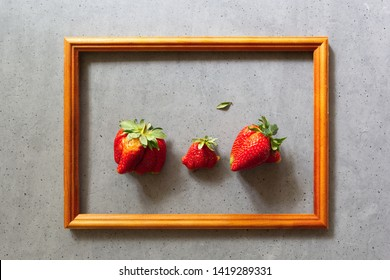 Ugly food. Organic homegrown strawberries in wooden frame on grey background. Funny imperfect fruits and vegetables, misshapen produce, individuality, food waste concept. Top view, copy space