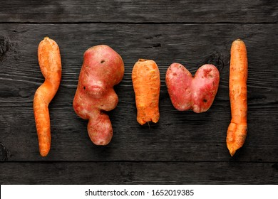 Ugly funny vegetables, heart-shaped potatoes and twisted carrot on a black wooden background. The concept of grungy vegetables or food waste. Top view, low key, copy space.